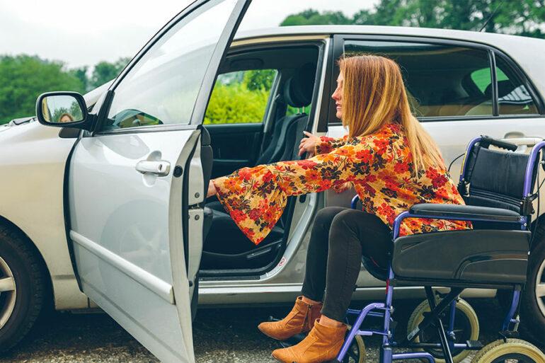 Donna disabile su sedia a rotelle entra in auto